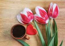 Tulips with cup of coffee. Tulips with a cup of coffee on a wooden background Stock Photos