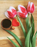 Tulips with cup of coffee. Tulips with a cup of coffee on a wooden background Royalty Free Stock Images