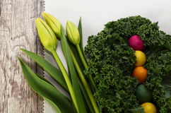 Tulips, curly kale and colorful candy. On a white linen napkin Royalty Free Stock Photos