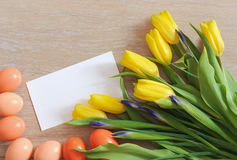 Tulips, Easter eggs and white paper lying on wood Stock Image