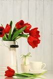 Tulips and egg with bow on table Royalty Free Stock Photo