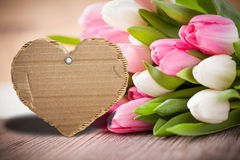 Tulips with empty message cardboard for own message. Tulips with empty message cardboard shaped as a heart for own message royalty free stock photography