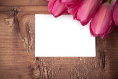 Tulips flowers with greeting card over wooden table Royalty Free Stock Images