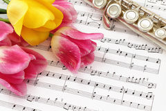 Tulips, Flute and Sheet Music. Pink and yellow tulips and flute lying on the sheet music Royalty Free Stock Photography