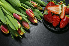 Tulips and fresh strawberries on black background Royalty Free Stock Photos