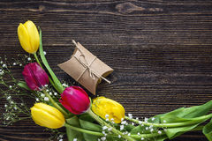 Tulips and gift box on dark wooden background. Top view with cop Royalty Free Stock Photos