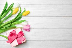 Tulips and gift box on wooden background. Top view Royalty Free Stock Photos