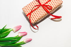 Tulips and gift package with a red bow Royalty Free Stock Photography
