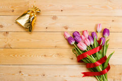 Tulips and gift on wooden texture Royalty Free Stock Photos