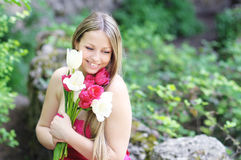 Tulips and a girl. Girl's holding tulips and smile Royalty Free Stock Photography