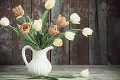 Tulips in glass vase on wooden background Royalty Free Stock Images