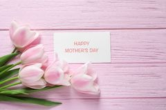 Tulips and greeting card with phrase. `Happy Mother`s Day` on wooden background Royalty Free Stock Photos