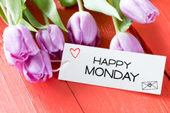 Tulips with happy monday card. Tulips with happy monday on paper card on wooden background royalty free stock image