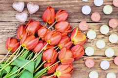 Tulips and a heart candles. Bunch of fresh red tulips lying alongside a heart candles of colorful candles for a loved one or sweetheart on Valentines Day or an Stock Images
