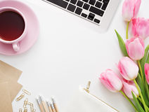 Tulips, keyboard and office supplies on white board Royalty Free Stock Images