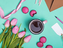 Tulips, macarons, ribbon and coffee in pink mug Royalty Free Stock Photography