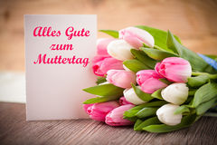 Tulips with message saying Best wishes for Mother's Day in German. Bouquet of tulips with message saying Best wishes for Mother's Day in German stock images