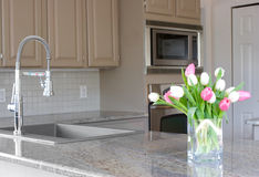 Tulips in a modern grey kitchen. Pink and white tulips in a modern grey kitchen Royalty Free Stock Image