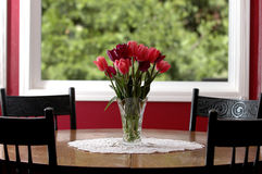 Tulips on my table. April tulips in a vase on a wooden kitchen table Stock Photo