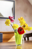 Tulips and narcissus  flowers in a green glass vase on a wooden table Royalty Free Stock Photo