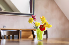 Tulips and narcissus  flowers in a green glass vase on a wooden table Royalty Free Stock Image