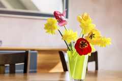 Tulips and narcissus in a green glass vase on a wooden table Royalty Free Stock Photo