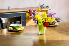 Tulips,narcissus and lilac  flowers in a green glass vase on a wooden table Royalty Free Stock Photo