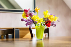 Tulips,narcissus and lilac flowers in a green glass vase on a wooden table royalty free stock images