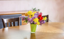 Tulips,narcissus and lilac  flowers in a green glass vase on a wooden table Royalty Free Stock Image