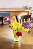 Tulips,narcissus and lilac  flowers in a green glass vase on a wooden table Stock Photos