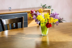 Tulips,narcissus and lilac  flowers in a green glass vase on a wooden table Royalty Free Stock Photography