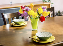 Tulips,narcissus and lilac  flowers in a green glass vase on a wooden table.table arrangement Royalty Free Stock Photography