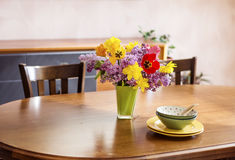 Tulips,narcissus and lilac  flowers in a green glass vase on a wooden table.table arrangement Royalty Free Stock Images