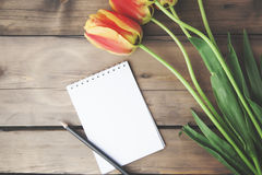 Tulips and notepad. On wooden table Stock Images