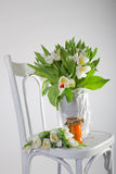 Tulips, orange and pumpkin marmalade on old chair Stock Photography
