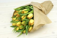 Tulips in a paper bouquet on wooden table royalty free stock photography