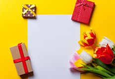 Tulips and paper with gifts on yellow Stock Image