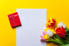 Tulips and paper with gifts on yellow Royalty Free Stock Images
