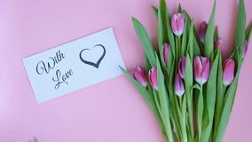 Tulips on pink background. Woman putting greeting card with the text WITH LOVE. Directly above view stock video