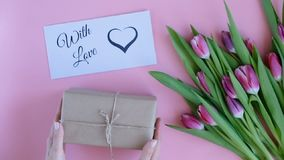 Tulips on pink background. Woman putting greeting card with the text WITH LOVE and a gift. Directly above view stock footage