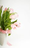 Tulips with a ribbon. Pink tulips with ribbon in vase stock photography