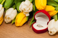 Tulips and silver engagement ring on a wooden background Royalty Free Stock Photos