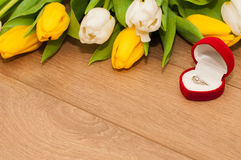 Tulips and silver engagement ring on a wooden background Stock Photography