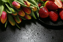 Tulips and strawberries with water drops Stock Photography