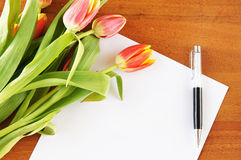Tulips on the table and empty paper sheet Stock Photo