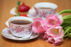 Tulips and tea. Couple of cups with tea, strawberries and tulips Royalty Free Stock Images