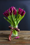 Tulips in a vase on brown boards Stock Photography