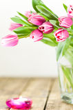 Tulips in vase and burning candle Stock Images