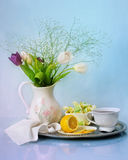 Tulips in a vase on a table. And a cup of tea Royalty Free Stock Images
