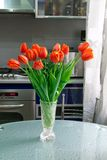 Tulips. In the vase at the table on the kithen background Royalty Free Stock Photo